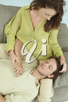 Young couple resting together on couch at home, embracing. Hing angle shot.