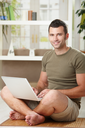 Casual man using laptop computer at home sitting on floor in living room, smiling.