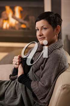 Woman sitting on sofa at home on a cold winter day, drinking hot tea, looking away.
