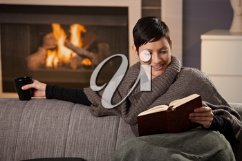 Woman sitting on sofa at home on a cold winter day, reading book.