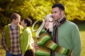Young love couples hugging and walking in park outdoor at autumn, smiling.
