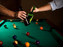 Men clinking beer bottles at snooker table, while playing game.