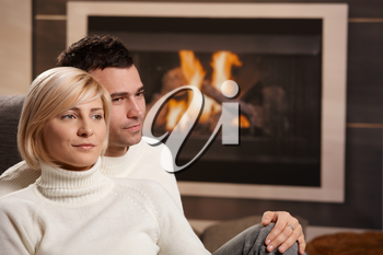 Young couple hugging on sofa in front of fireplace at home, looking away, smiling.
