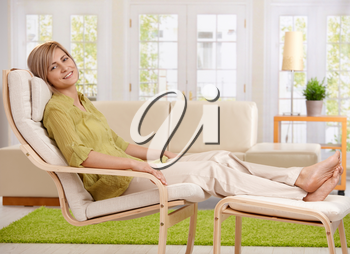 Woman relaxing at home, sitting in armchair with crossed feet up on footboard, smiling at camera.