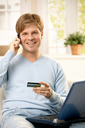 Smiling man talking on mobile phone, holding creditcard, sitting on couch with laptop computer, looking at camera