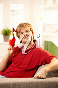 Young man holding red female slipper in hand sitting on couch looking affectionate.