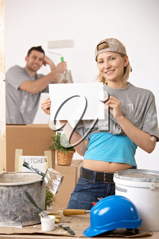 Smiling couple painting new house, blank page for copyspace.