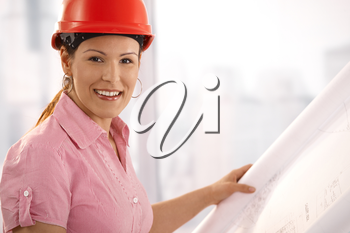 Portrait of female architect holding floor plan, looking at camera, smiling.