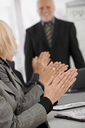 Clapping hands in closeup focus on businessmeeting, senior businessman standing in background.