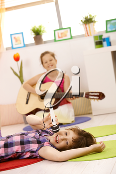 Portrait of schoolgirls playing music, one singing with microphone, other playing guitar, smiling.