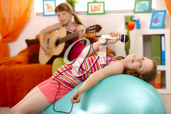Young girl singing with microphone, posing on gym ball, smiling, friend playing guitar in background.