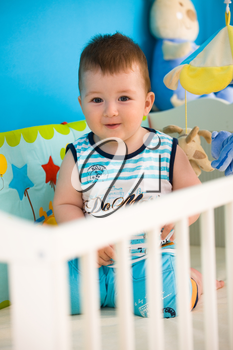 Happy baby boy ( 1 year old ) playing in baby bed at children's room, smiling.
