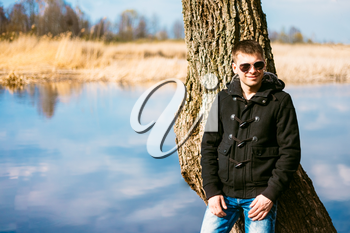 Young Handsome Man Leaned Against A Tree By River In Autumn Day, Smiling In Camera. Casual Style - Jeans, Jacket, Sunglasses