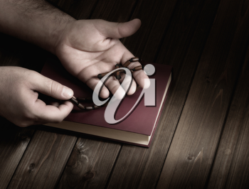 wooden Christian cross in his palms on the Bible during prayer.