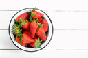 fresh ripe strawberries in a bowl on white wooden table