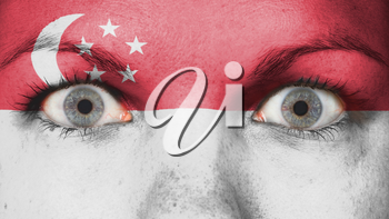 Close up of eyes. Painted face with flag of Singapore