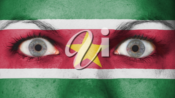 Close up of eyes. Painted face with flag of Suriname