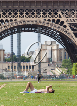 PARIS - July 27, 2013: Tourist is sunbathing on July 27, 2013 near the Eiffel tower in Paris, France. The tower is an 1889 iron lattice tower which stands at 324 meters. PARIS, July 27, 2013