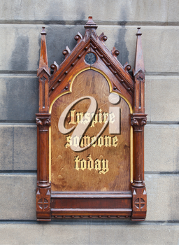 Decorative wooden sign hanging on a concrete wall - Inspire someone today