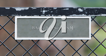 Sign hanging on an old metallic gate - Back to school