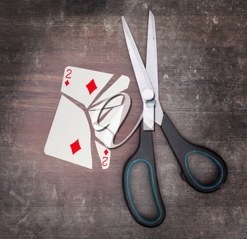 Concept of addiction, card with scissors, two of diamond