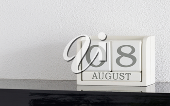 White block calendar present date 8 and month August on white wall background