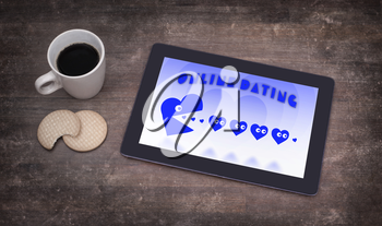 Online dating on a tablet - concept of love, blue pacman eating hearts