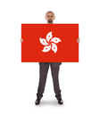 Smiling businessman holding a big card, flag of Hong Kong, isolated on white