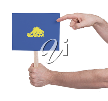 Hand holding small card, isolated on white - Flag of Oregon