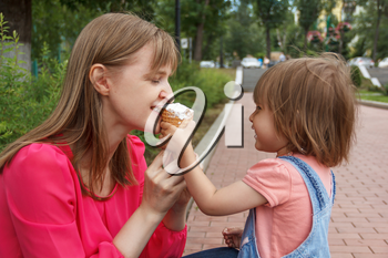 Photo of cute baby girl feeding mother icecream in summer