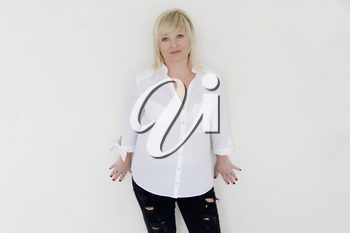 Blond woman in white and black jeans stand inside empty room
