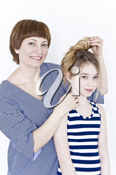 Mother is making hairstyle to her daughter near white wall in striped clothes