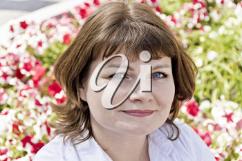 Beautiful smiling woman in white on flowers background