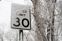 road sign of limit of speed under snow