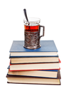 glass of tea on stack of books isolated on white background
