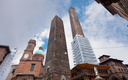 palace and two towers and statue of Saint Petronius under cloudy sky in Bologna, Italy