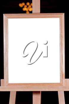 wooden picture frame with white cut out canvas on easel