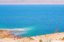 panorama with people on sand beach of Dead Sea, Jordan