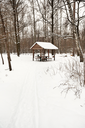 snow covered wooden pavilion in urban park in winter