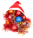 christmas giftsl - xmas balls and decorations fall out from red santa hat on white background