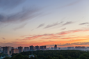 blue sky with orange sunlight over city at summer dawn