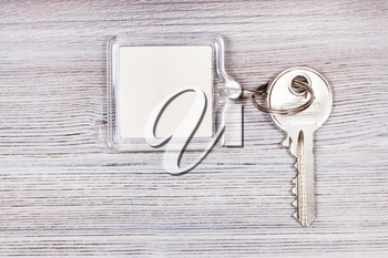 door key with white blank key chain on wooden board