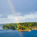 green island with village in Baltic Sea and rainbow in blue sky in sunny autumn day, Sweden