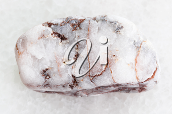 macro shooting of natural mineral rock specimen - tumbled marble gem on white marble background from Greece