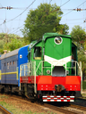 Green locomotive and blue passenger cars on the rails taken closeup.