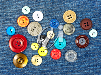 Various sized multicoloured buttons on blue fabric as background.