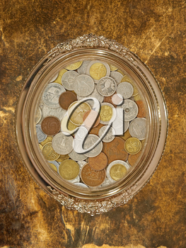 Golden oval photo frame with numismatic coins collection inside on grungy wall.