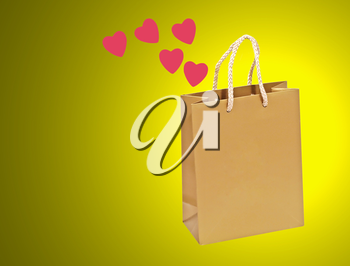Empty golden valentines gift bag on a yellow background.