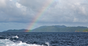 from a boat the rainbow from  ocean and island in background