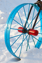 Metallic painted detail in the form of a bicycle wheel in the snowdrift in winter season outside